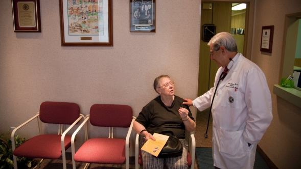 A doctor talks with a patient in his waiting room.