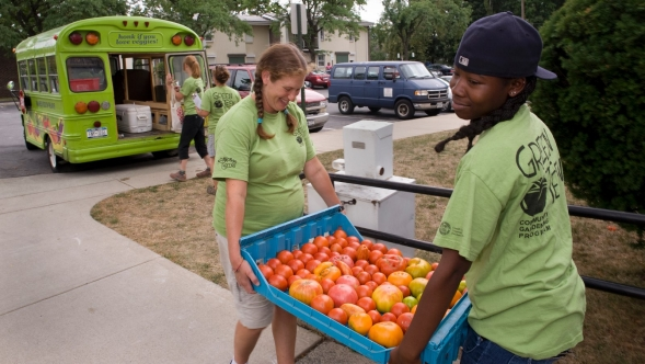 High school students carry tomatoes to a van.