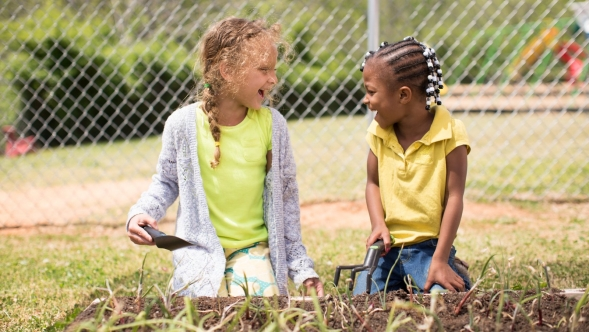 Two young girls gardening.