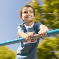 A caucasian boy rides a moving merry go round at an outdoor playground.