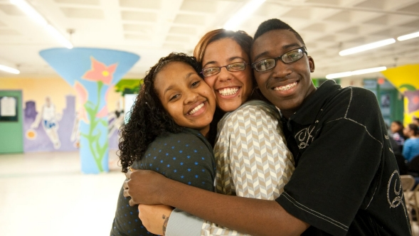 Three teens embrace in a school setting.