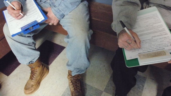 Patients complete paperwork in a waiting room.