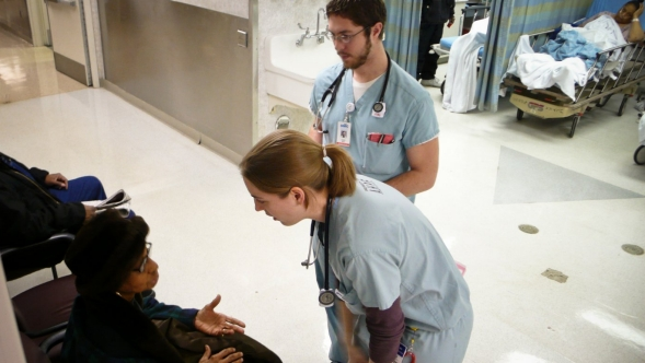 A hospital doctor checks a young girl using an auriscope.
