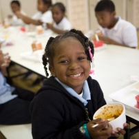 Smiling students eat a healthy meal in their school cafeteria.