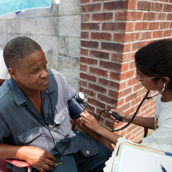 A man receives blood pressure screening at a health fair.