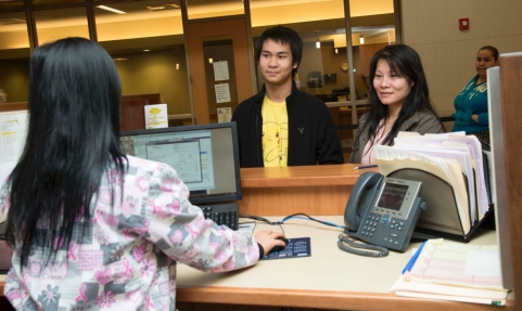 Couple at front desk of the HealthFirst Family Care Center.