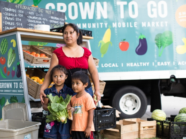 A family stands next to a mobile market.