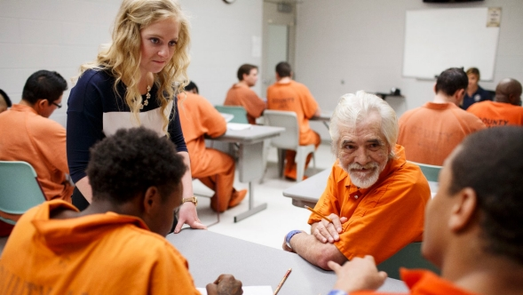 Volunteer works with a inmates at the Spartanburg County Detention Center during an art class.