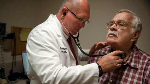 Doctor listening to patient's pulse.