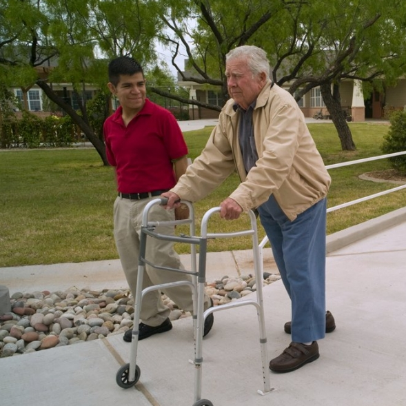 A care giver and an elderly man using a walker, walking outside.