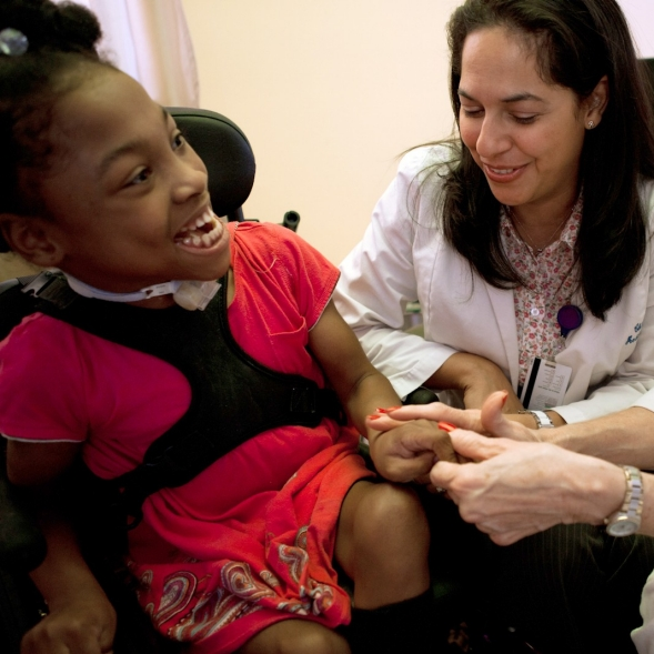 Two medical professions sit holding hands with a young disabled girl.