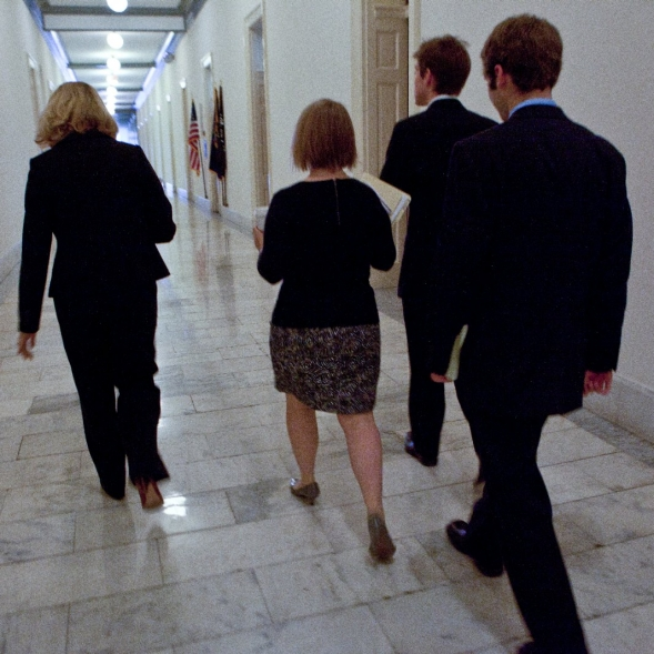 Employees walking down a hallway in a government building.