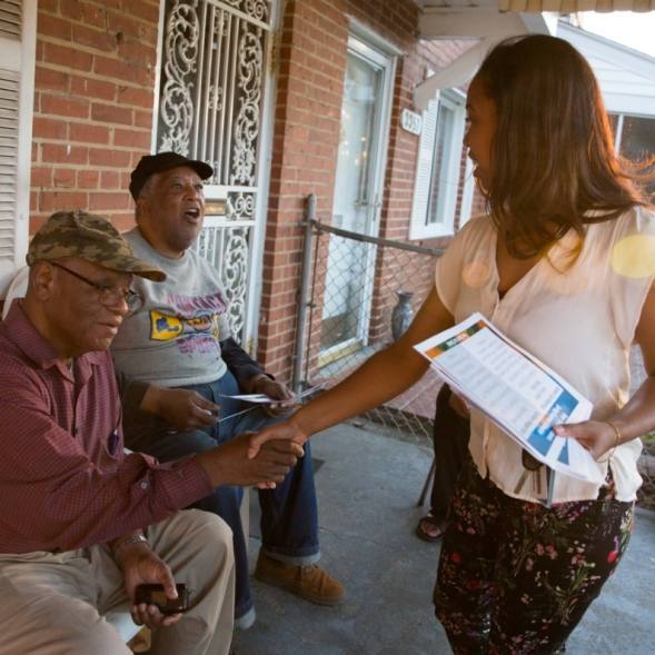 A woman shares information with two men on a front porch.