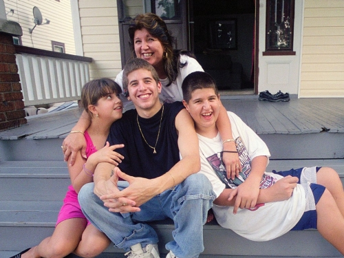 A family sits on the front stoop of their house.