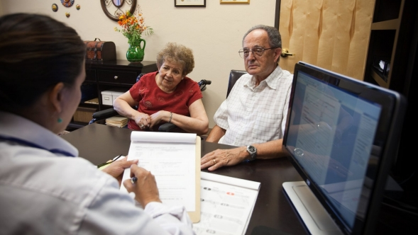 An elderly couple talks with a doctor in her office.