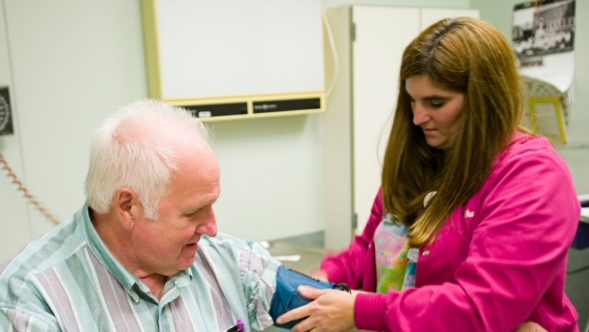 A medical assistant checks a patient's blood pressure.