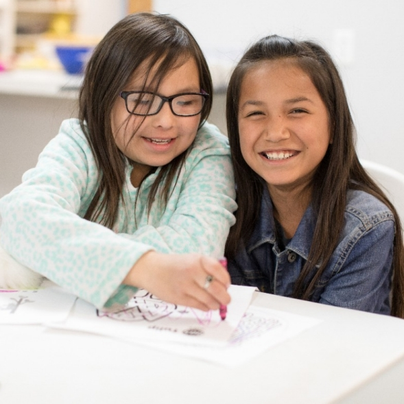 Two girls smiling, drawing with crayons.