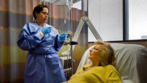 A nurse with a cancer patient who is receiving chemo therapy.