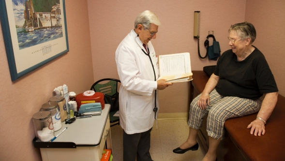 A doctor reads a patient's records during a check up.