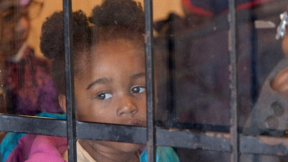 Girl looks out a barred window.