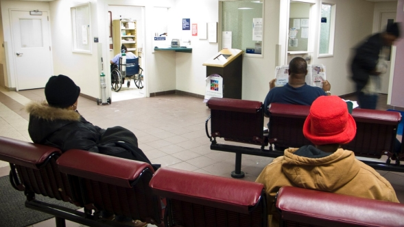 A man waits in a hospital waiting room.